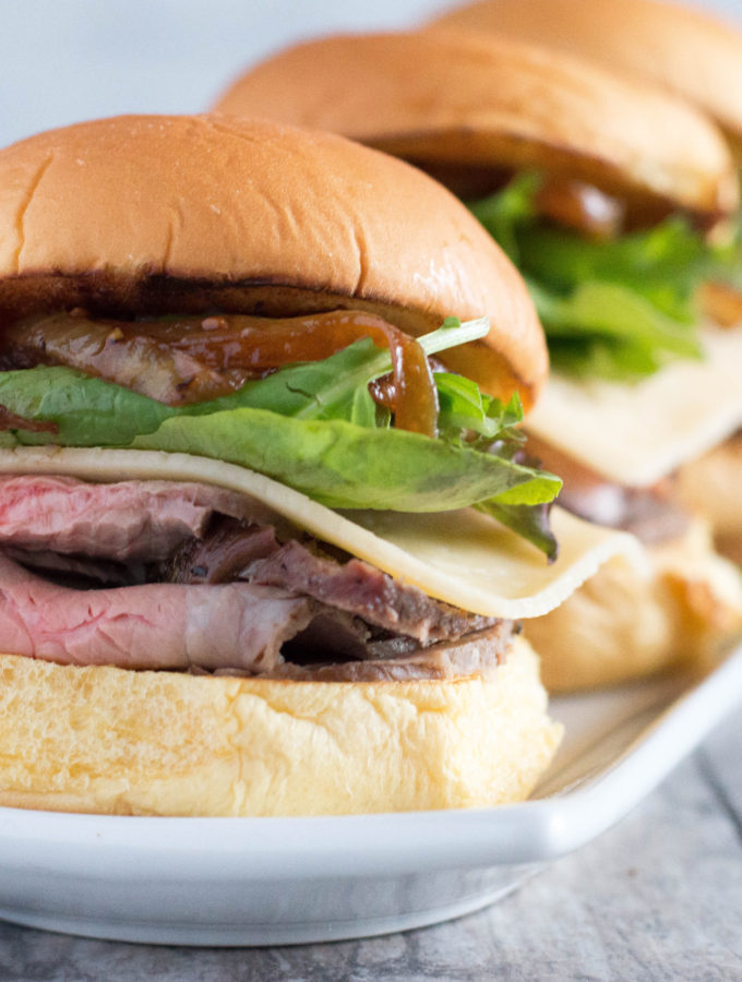 Easy Roast beef sliders topped with gouda cheese, spring mix and caramelized onions