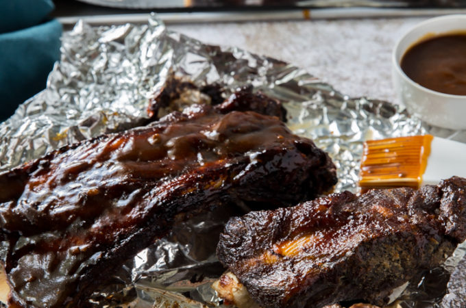 easy instant pot beef ribs cooked topped with low carb BBQ sauce on aluminum foil