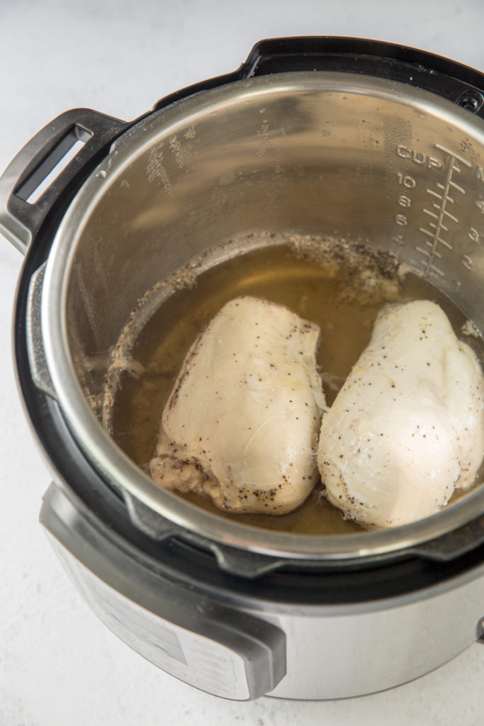 instant pot with cooked chicken breasts in it