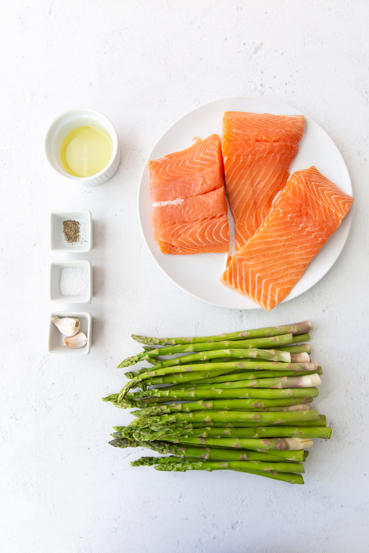 salmon on a white plate, asparagus, oil and spices