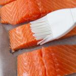 brushing oil onto salmon filets
