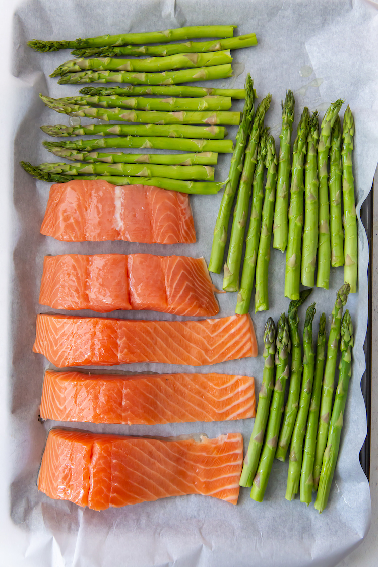 salmon and asparagus on a parchment lined cookie sheet