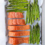 raw salmon and uncooked asparagus on a parchment lined cookie sheet topped with spices