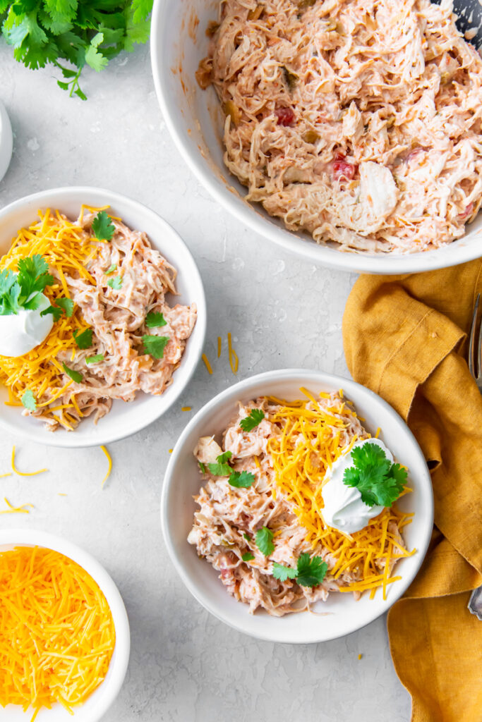 creamy salsa chicken recipe topped with shredded cheese, sour cream and cilantro