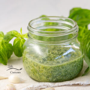 square crop of a glass jar filled with pesto and fresh basil leaves around.