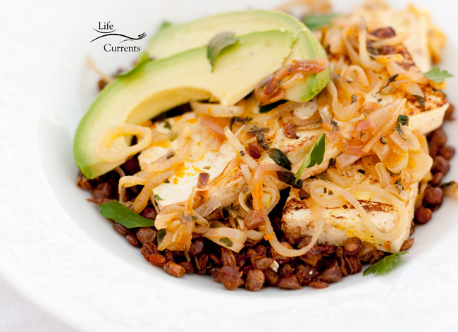 Orange-Shallot Tofu with Avocado Served on a Bed of Roasted Lentils - with avocados, tofu, shallots, all over chipotle lentils in a bowl
