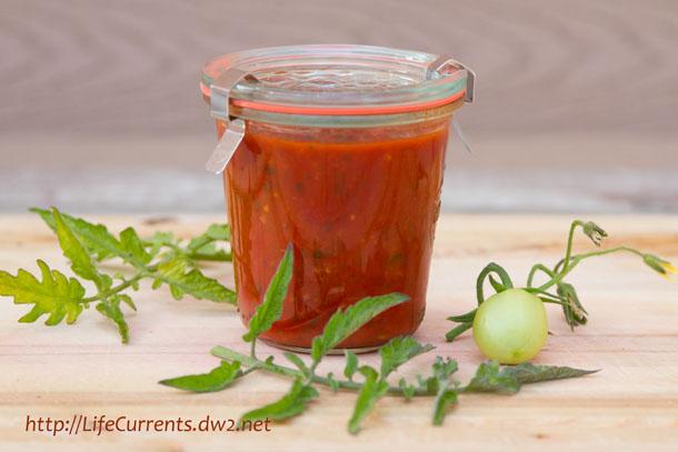 marinara in a jar with tomato plants around it