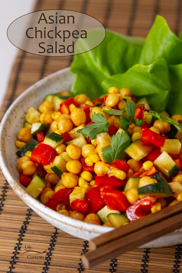 Asian Garbanzo Bean Salad in a white bowl with lettuce leaves and chopsticks, title on image.