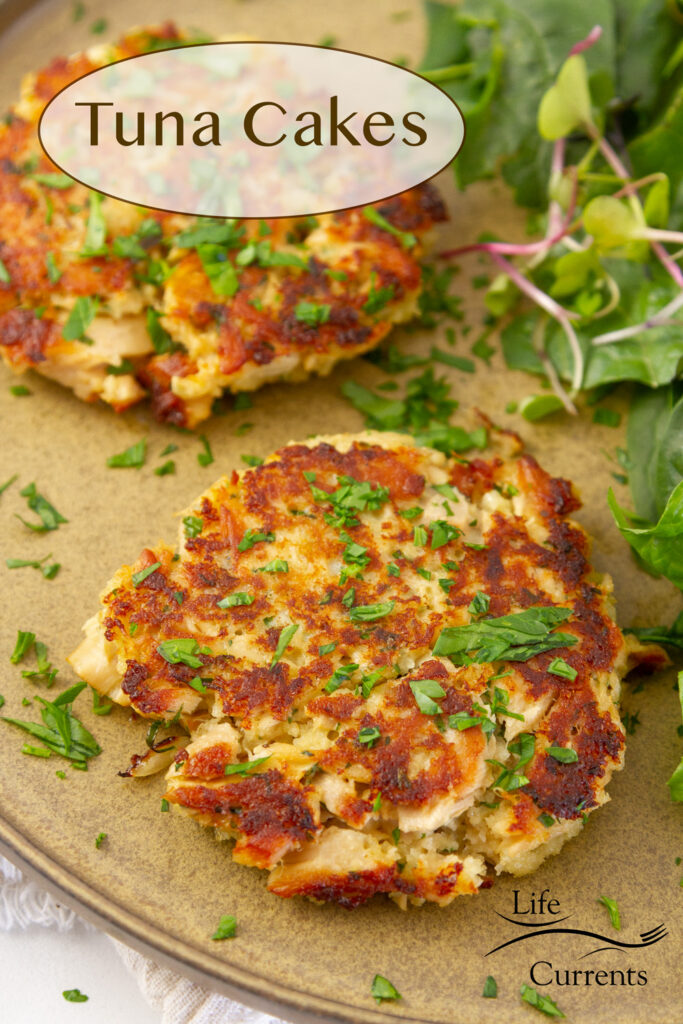 two tuna cakes on a plate with fresh herbs and geens, title on upper left.