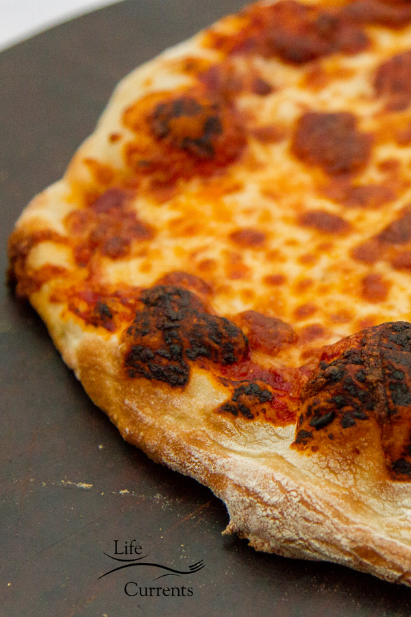 Homemade Thin Crust Pizza on a dark colored pizza stone
