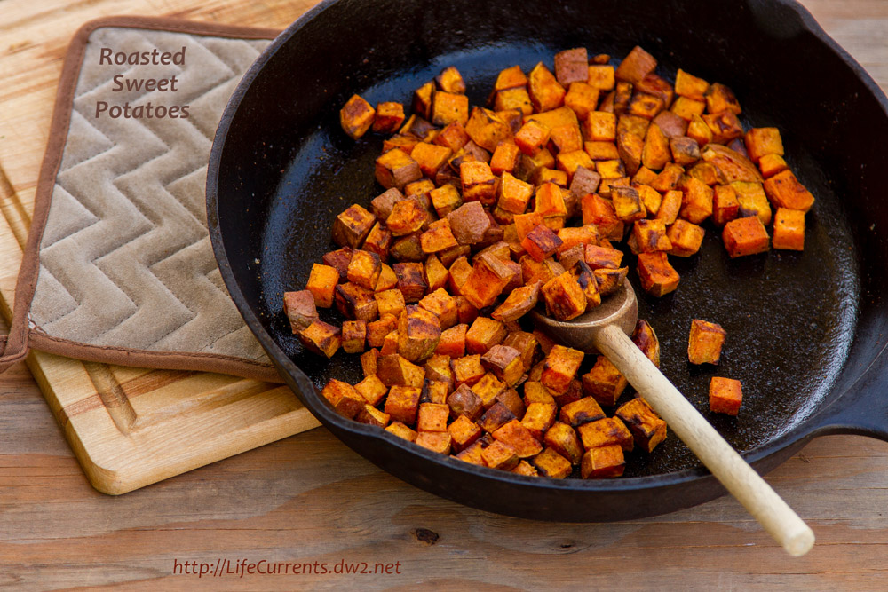 cubes of sweet potatoes in a cast iron skillet with a wooden spoon