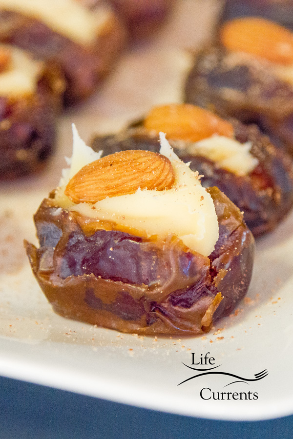 Medjool dates stuffed with Mascarpone, an almond, and garnished with freshly ground nutmeg on a white plate