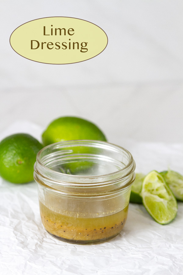 lime dressing in a small mason jar with limes around it plus squeezed lime wedges.