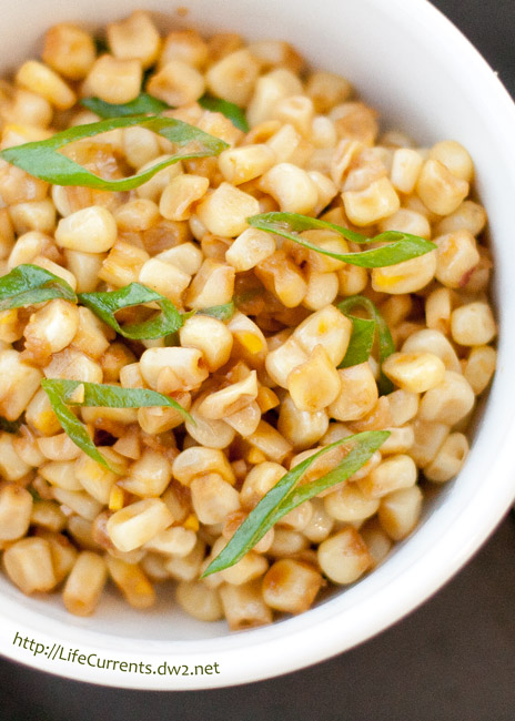 corn garnished with green onions in a white bowl.