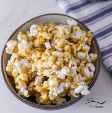 a bowl of caramel corn with a blue striped towel in the background