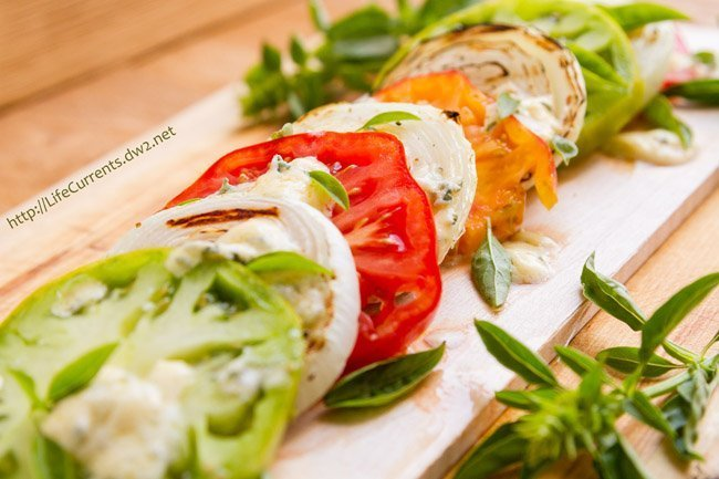 tomato slices, basil, onion slices, and blue cheese