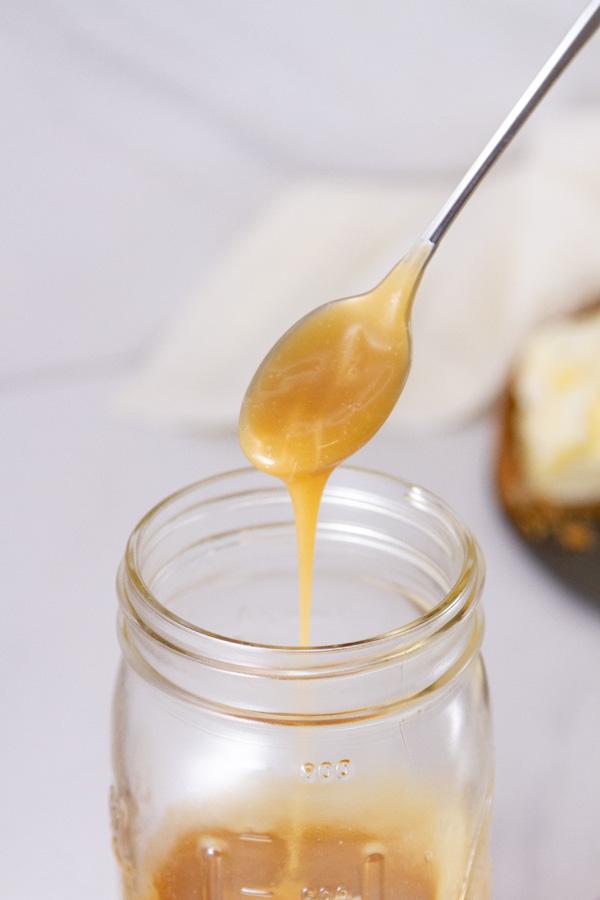 a spoon pouring caramel sauce into a mason jar.