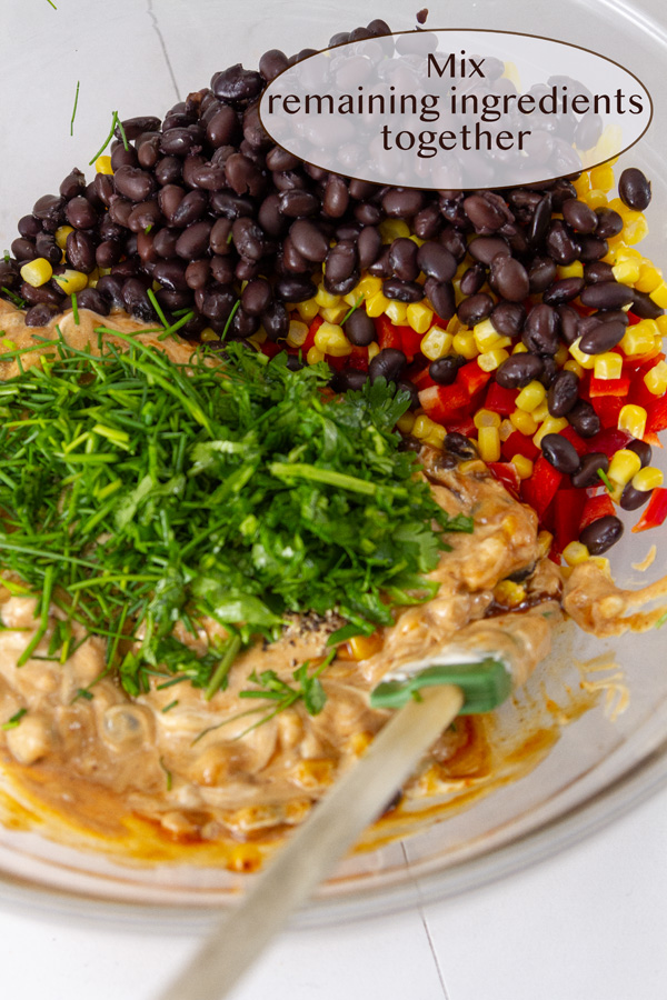 black beans, red pepper, corn, sauce, and herbs in a bowl with a spoon.