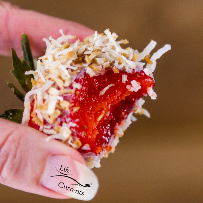 Coconut Dipped Strawberries - a fresh ripe berry has a bite eaten out of it showing the beautiful red fruit