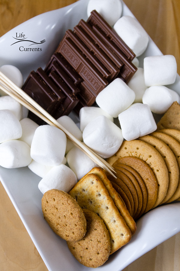 A s'mores tray with dark chocolate, milk chocolate, different kinds of crackers and cookies, marshmallows, and skewers