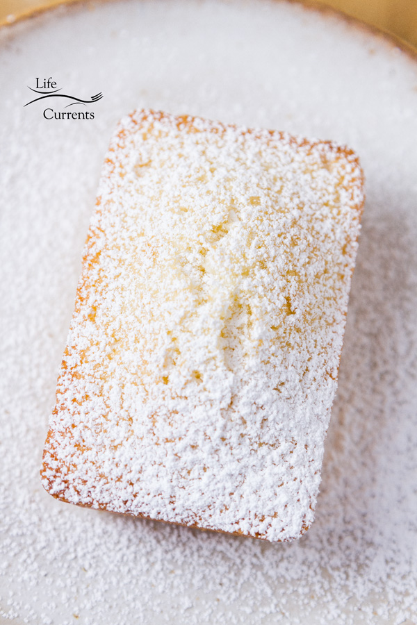 A tea cake dusted with powdered sugar on a white plate