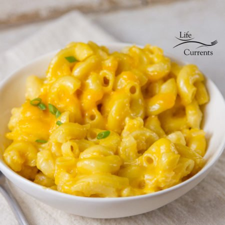 A white dish of cheddar mac & cheese with green onions garnishing on a white background