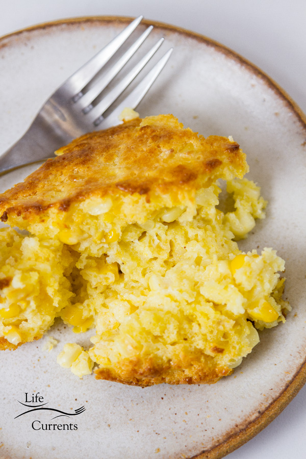 A serving of corn casserole on a white plate with a fork