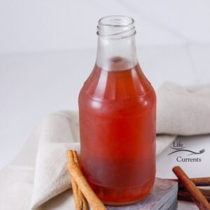 a square image of a glass jar filled with Cinnamon Simple Syrup