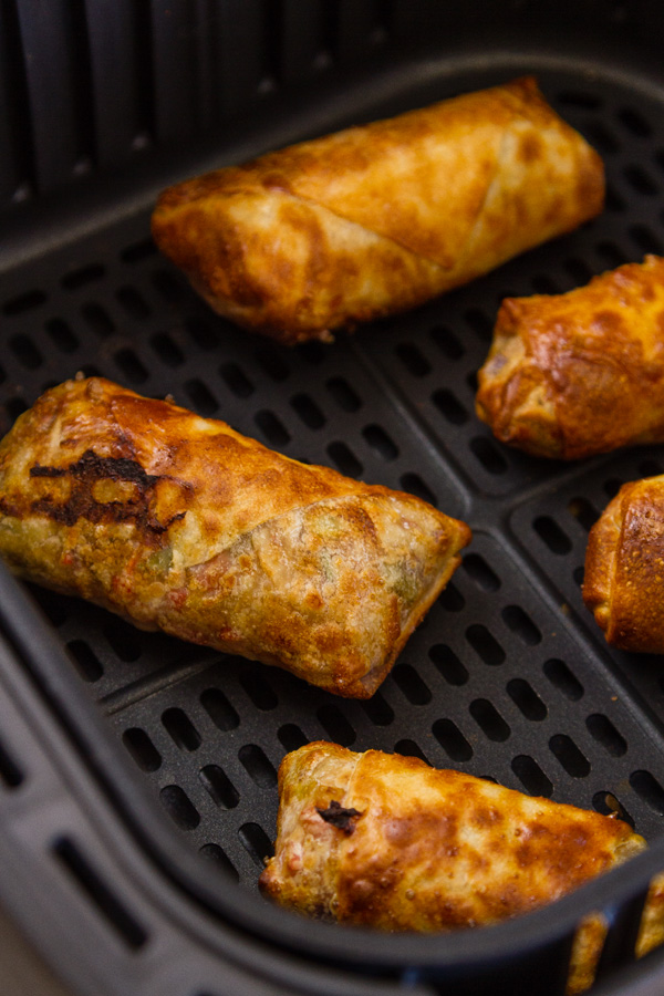 Egg Rolls in the basket of an air fryer