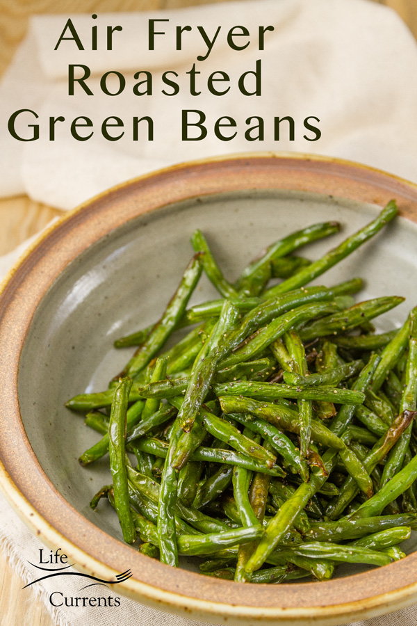 Green beans that were roasted in the air fryer in a ceramic bowl with a napkin and the title is on the image