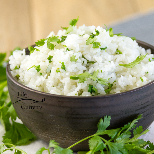 a black bowl full of rice with cilantro around it