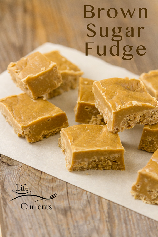 Pieces of brown sugar fudge on parchamnet paper on a wooden background