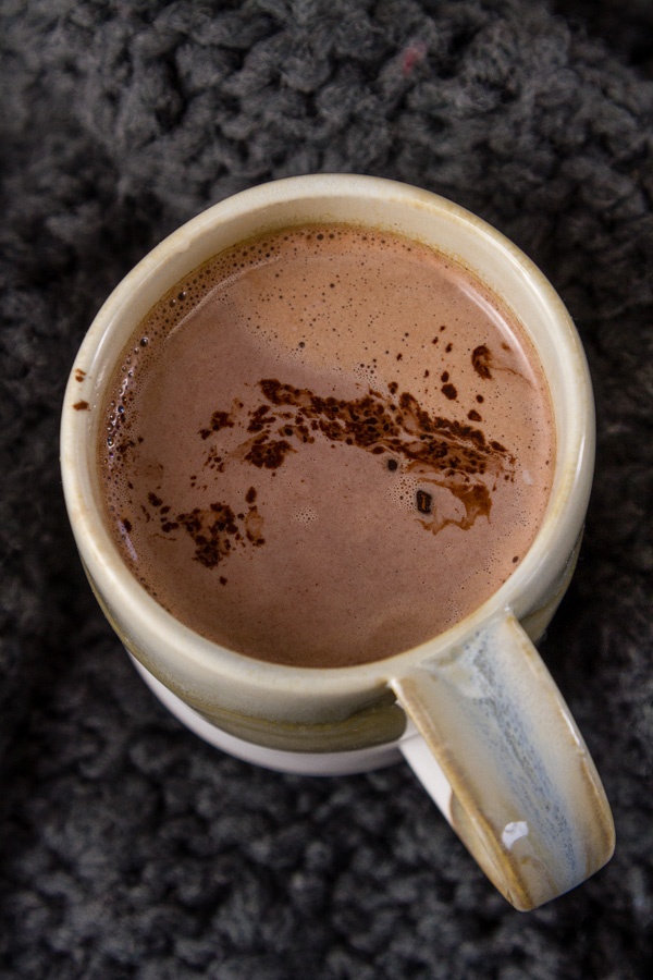 a mug full of hot cocoa topped with a pinch of cocoa on a gray knitted cloth background