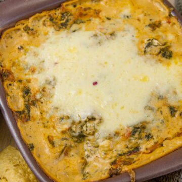 vertical image of Cheesy Fiesta Spinach Dip with tortilla chips