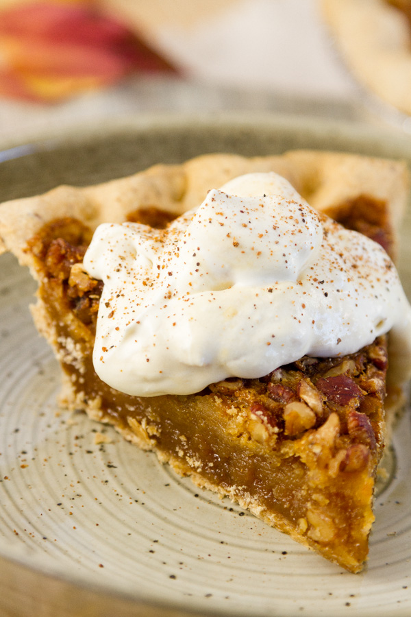 American Bourbon Pecan Pie from Millican Pecan Company with peach whipped cream on a plate with fall leaves in the background