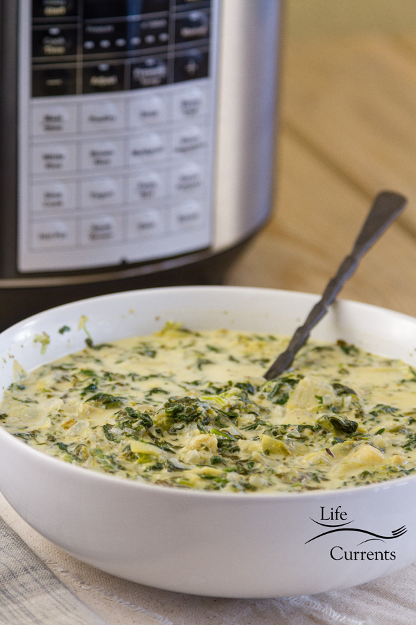 a pressure cooker in the background and a big bowl of spinach artichoke soup with a spoon in it