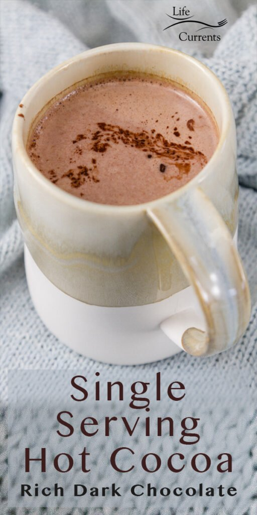 A mug filed with hot cocoa on a light blue knitted cloth