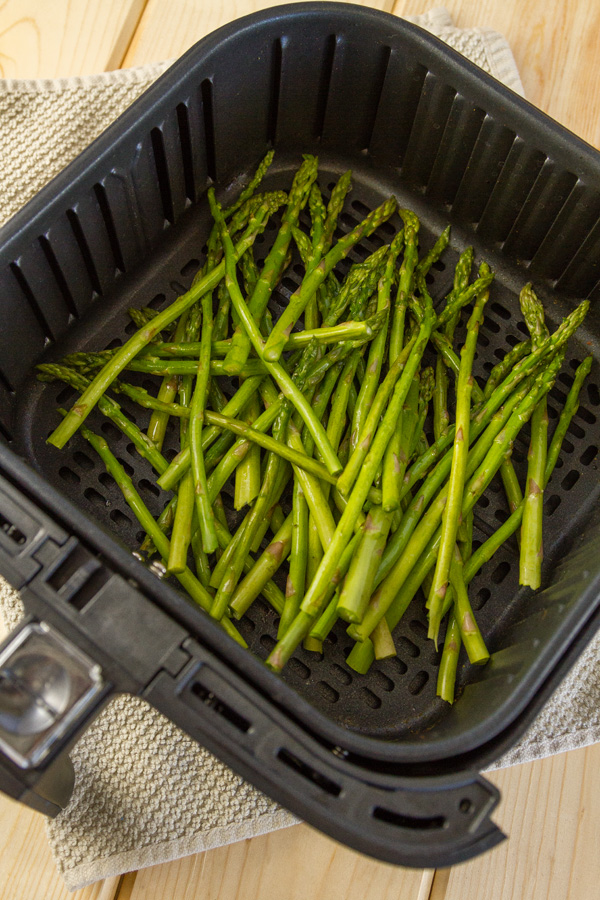 asparagus in the air fryer basket ready to cook
