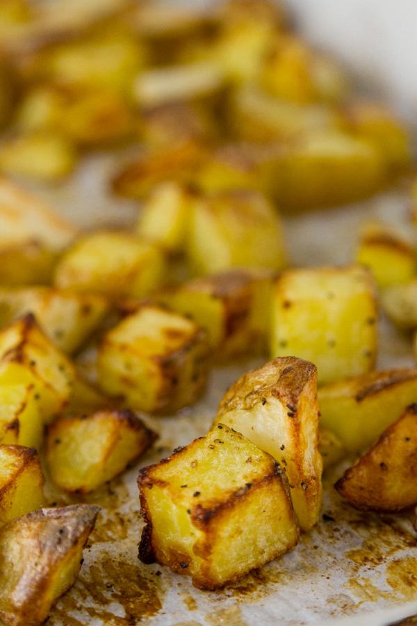 close up of Potato cubes still on the roasting sheet