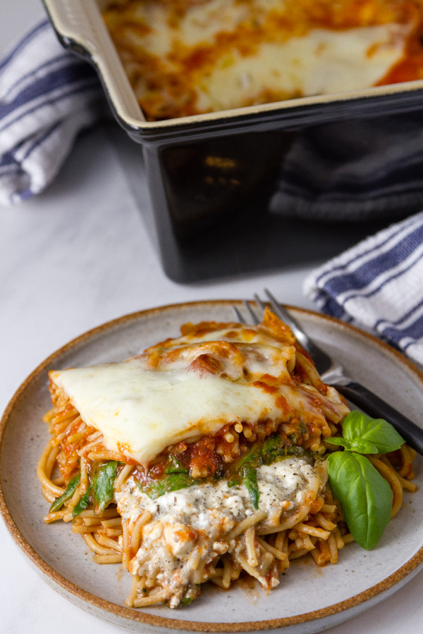A serving of Spinach Provolone Baked Pasta casserole on a white plate with a garnish of basil and the casserole is in the back with a blue towel