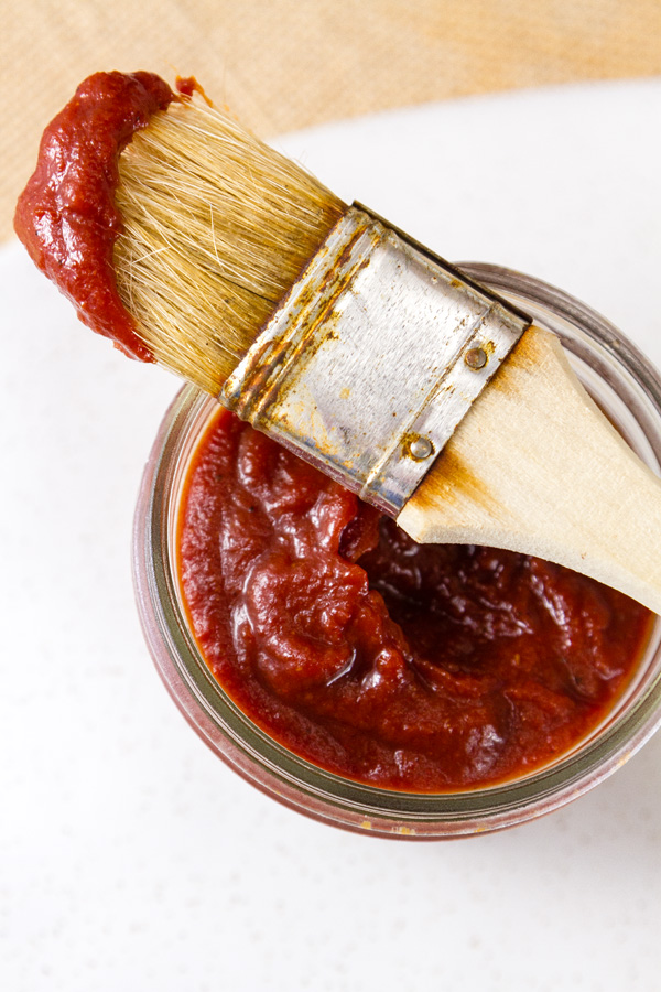 Top down view of a jar of BBQ sauce with a pastry brush on top. The brush has been dipped in the sauce