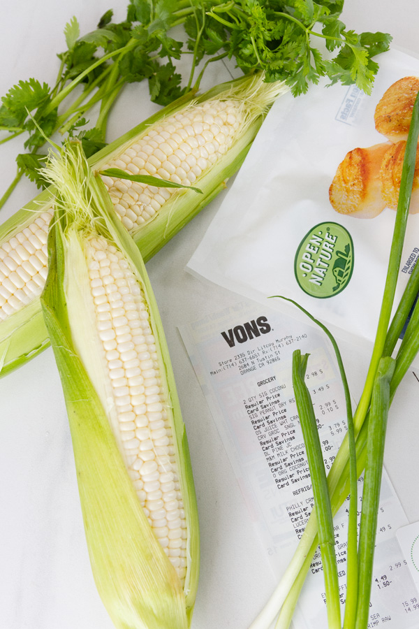 fresh ears of corn, a Vons reciept, a bag of Open Nature Seafood, and some green onions