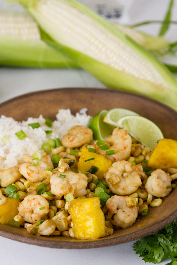 Foil Packet Caribbean Shrimp  served with coconut rice on a brown bowl with aears of corn in the background