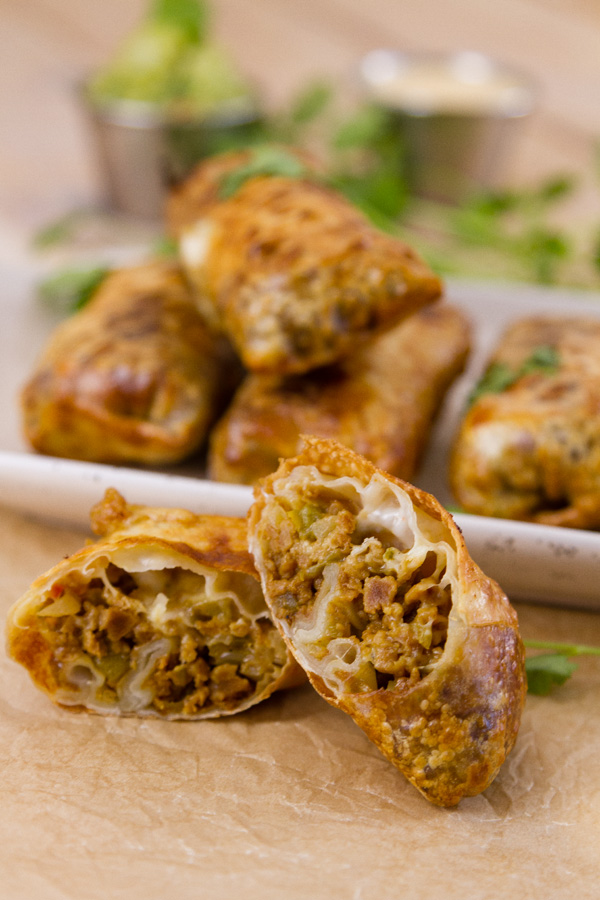a cut open egg roll in front so you can see the filling. In back, several egg rolls on a plate