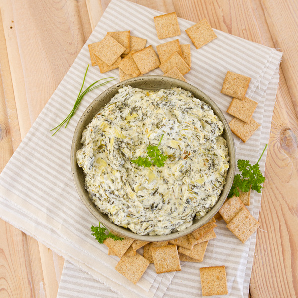 flat lay looking down into a bowl of spinach and artichoke dip served with crackers and garnished with parsley