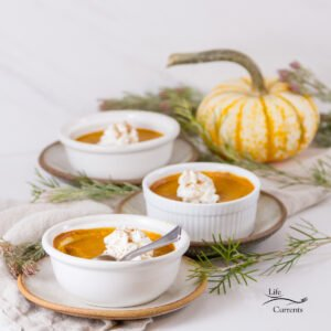 square crop of 3 custards on plates with a small pumpkin in the background