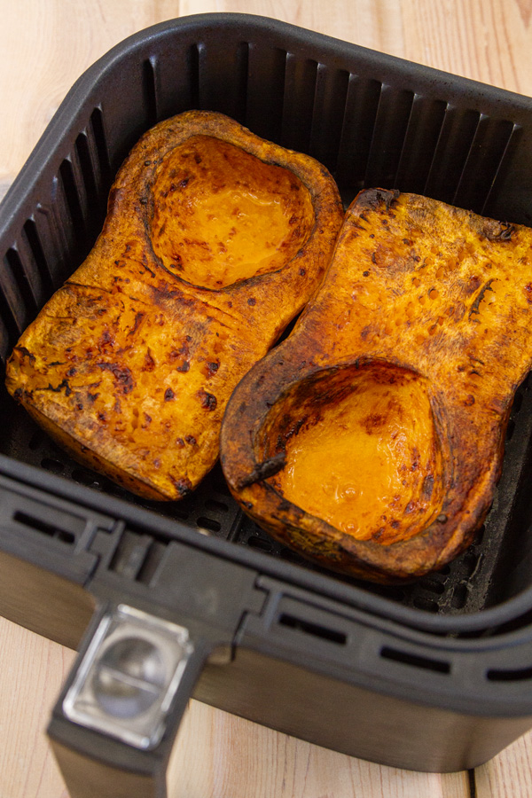 cooked butternut squash in the basket of an air fryer