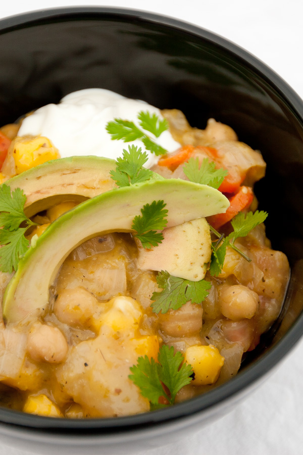 Vegetarian Stew in a black bowl with avocado and sour cream