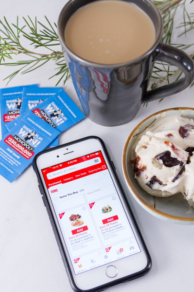 MONOPOLY game pieces with the Vons app showing their coupon page, a bowl of ice cream and some coffee in a cup