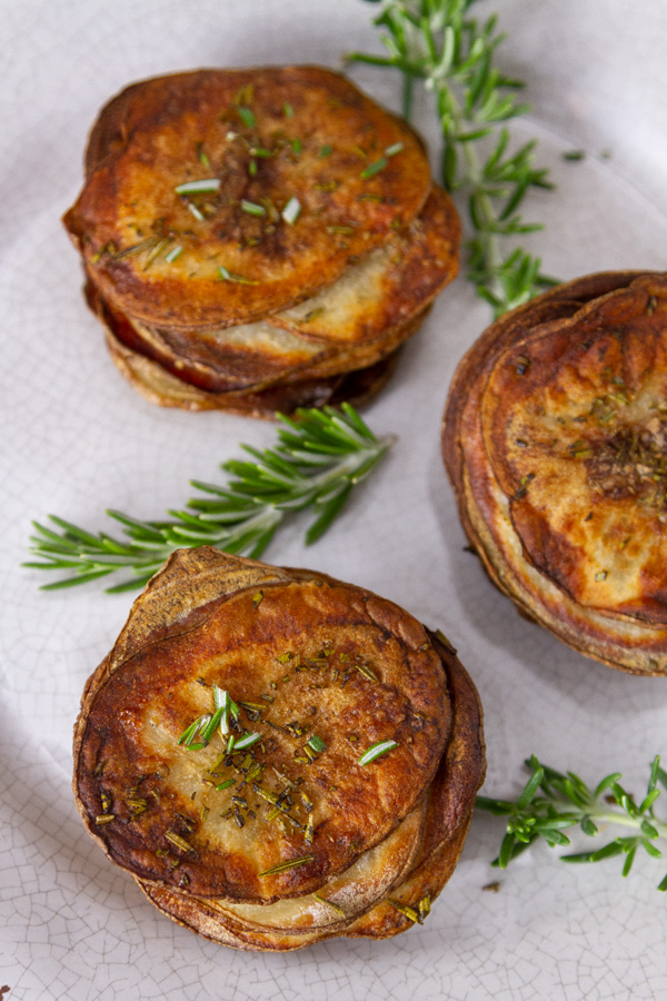 Three stacked cooked potatoes with rresh rosemary.